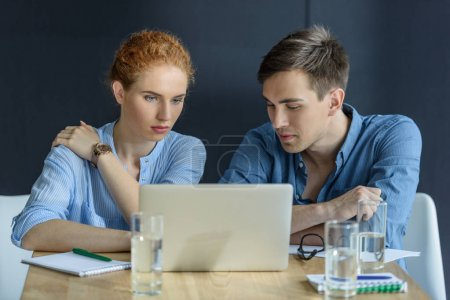 Photo for Thoughtful businessman and businesswoman working on project in modern office - Royalty Free Image