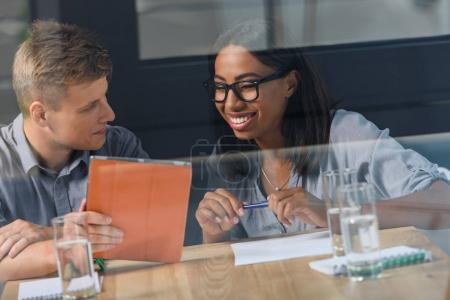Behind the glass view of smiling businessman and businesswoman discussing project in modern office
