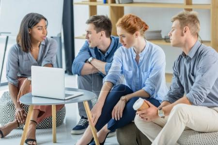 Successful team discussing project by laptop in modern office