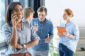 Young businesswoman talking on smartphone while business team discussing project in modern office