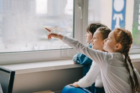 adorable schoolchildren looking at window together at classroom and pointing somewhere