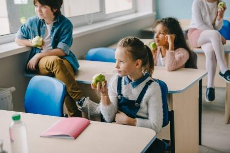 adorable schoolchildren eating apples at classroom while having break