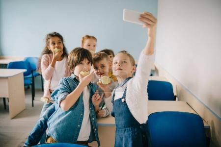 group of adorable kids taking selfie at school classroom