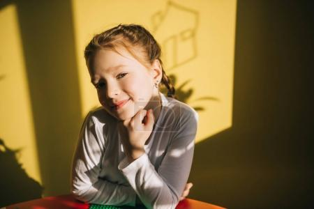 happy little child looking at camera indoor under sunset light