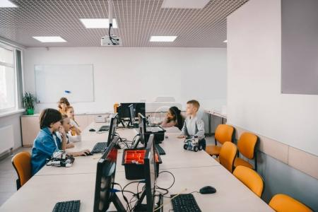 Photo for Group of kids working with computers on machinery class - Royalty Free Image