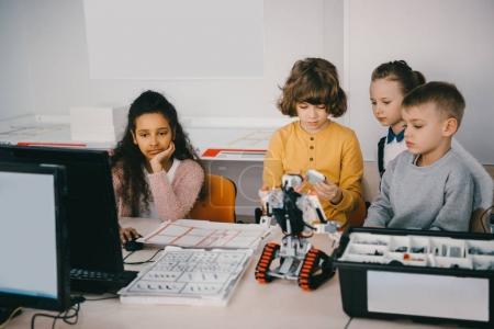 focused teen kids constructing diy robot at machinery class