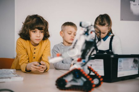focused teen kids constructing diy robot, stem education concept