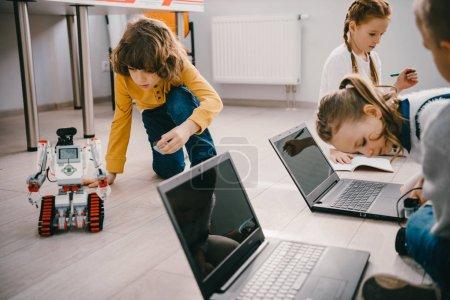 Photo pour Axé sur les enfants, programmation des robots avec des ordinateurs tout en étant assis sur le plancher - image libre de droit