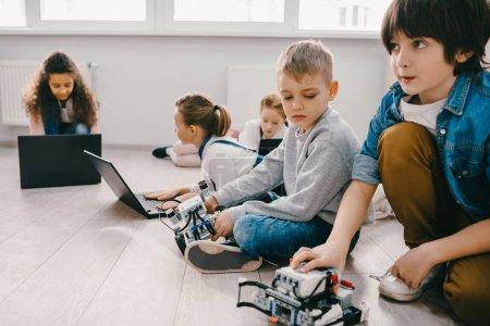 Foto de Concentrado niños programación robots con ordenadores portátiles mientras está sentado en el piso, vástago de concepto de educación - Imagen libre de derechos