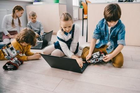 Photo for Kids programming robots with laptops while sitting on floor, stem education concept - Royalty Free Image