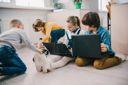 Photo for Happy kids working with laptops on floor, stem education concept - Royalty Free Image