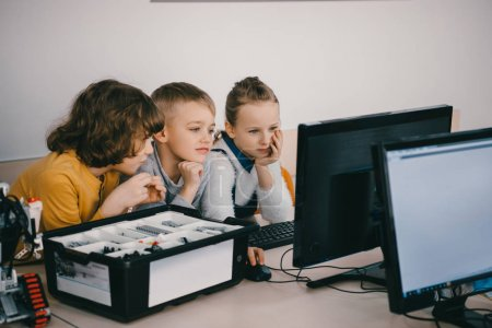 Photo for Focused kids working with computer together, stem education concept - Royalty Free Image