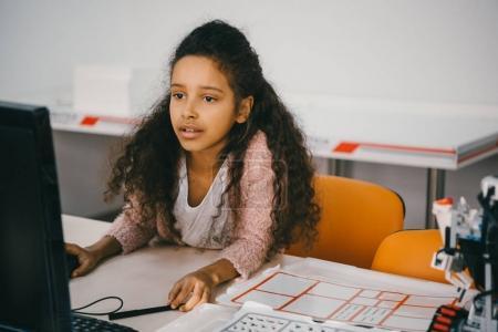 Photo pour Concentrée afro-américaine écolière travaillant avec ordinateur à la classe de machines - image libre de droit