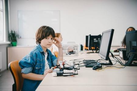 teen kid looking at camera while programming diy robot at machinery class