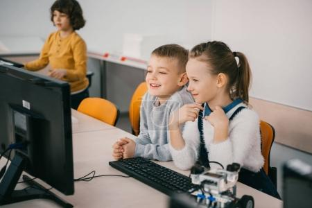 Foto de Niños felices trabajando con ordenador junto a la clase de maquinaria - Imagen libre de derechos