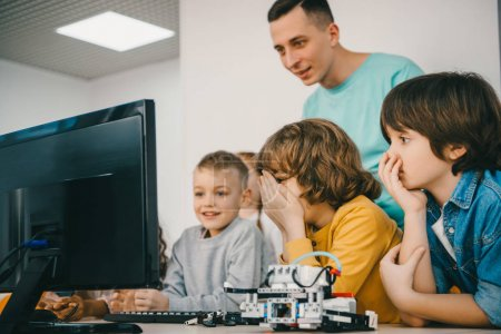 teacher programming robot with his teen students