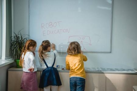 rear view of children writing and drawing robot education signs on whiteboard