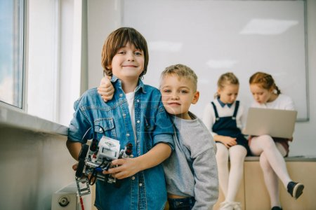 little kids with diy robot on machinery class