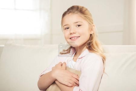 Photo pour Portrait de fille souriante décontractée tenant le livre et regardant la caméra tout en étant assis sur le canapé à la maison - image libre de droit
