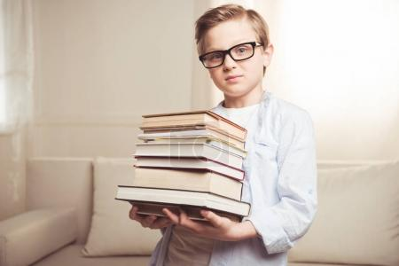 boy holding pile of book