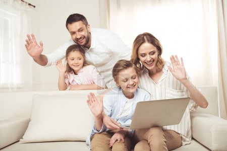 Photo for Happy family with two adorable children sitting together and using laptop at home - Royalty Free Image