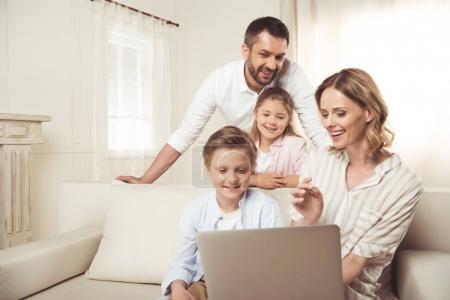 Foto de Familia feliz con dos niños adorables sentados juntos y usando el portátil en casa - Imagen libre de derechos