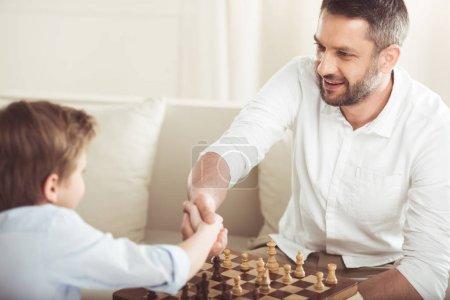 Photo pour Père et fils serrant la main après avoir joué au jeu d'échiquier - image libre de droit