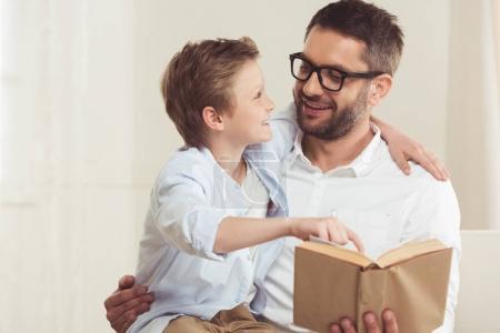Photo pour Portrait du père et du petit fils lisant le livre à la maison - image libre de droit