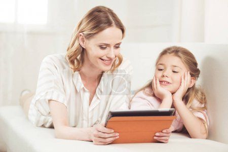 Photo pour Mère et fille souriantes utilisant une tablette numérique alors qu'elles sont allongées sur le canapé à la maison - image libre de droit