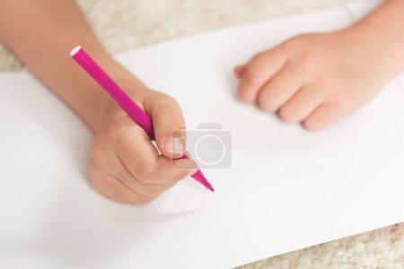 Photo pour Plan recadré de dessin d'enfant avec stylo feutre sur feuille de papier vierge - image libre de droit