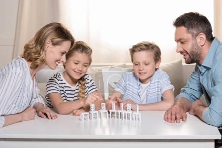 Photo for Smiling family sitting at table and playing with domino pieces - Royalty Free Image