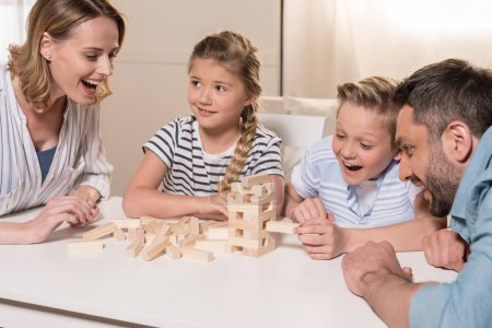 Photo for Smiling family playing Jenga game at home together - Royalty Free Image