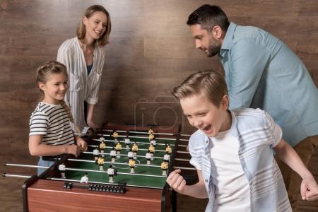 Foto de Happy sonriente familia jugando al futbolín juntos - Imagen libre de derechos