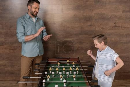 boy playing foosball with father