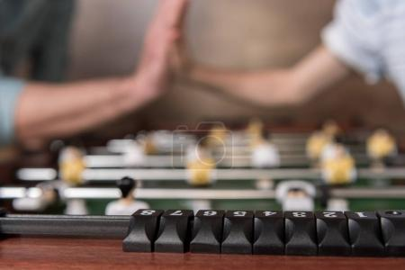 Photo for Close-up view of table football and hands giving high five on background - Royalty Free Image