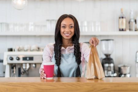 Photo for Smiling afro american waitress holding coffee to go and take away food in hands - Royalty Free Image