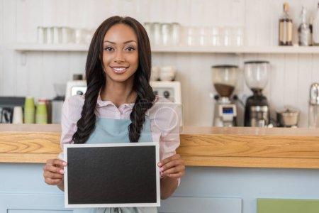 Photo pour Serveuse afro-américaine tenant le tableau vide et regardant la caméra tout en se tenant au café - image libre de droit