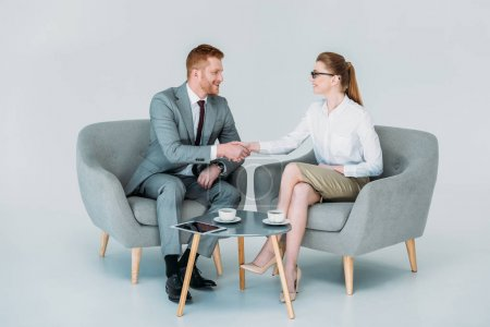 Photo for Businessman and businesswoman shaking hands while sitting in armchairs, isolated on white - Royalty Free Image