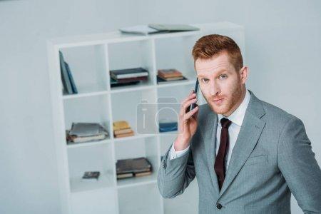 Foto de Hombre de negocios guapo en traje gris con smartphone en oficina - Imagen libre de derechos