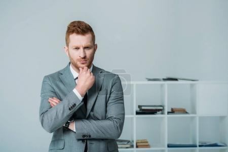 Photo for Handsome thoughtful businessman in grey suit standing in office - Royalty Free Image