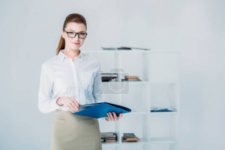 Photo for Attractive businesswoman with folder standing in modern office - Royalty Free Image