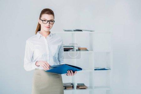 Photo pour Attrayant femme d'affaires avec dossier debout dans le bureau moderne - image libre de droit