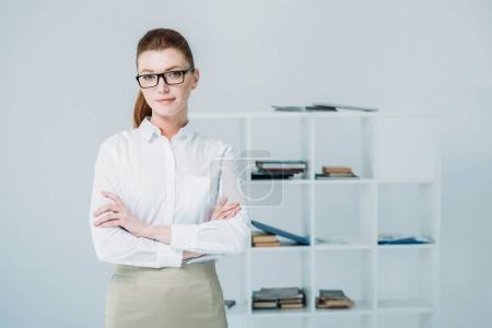 Photo for Beautiful businesswoman with crossed arms standing in modern office - Royalty Free Image