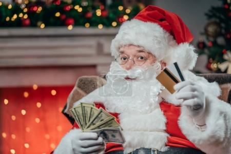 Photo for Santa claus in traditional red costume holding credit cards and dollar banknotes - Royalty Free Image