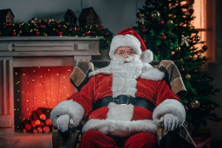 Photo for Bearded santa claus in traditional red costume sitting in armchair near fireplace - Royalty Free Image