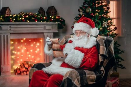 Photo for Santa claus in traditional red costume holding list - Royalty Free Image