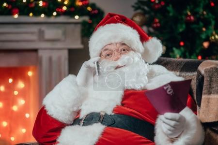 Photo for Bearded santa claus in traditional red costume talking on smartphone - Royalty Free Image