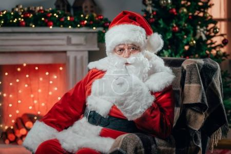 Photo for Angry santa claus in traditional red costume gesturing and sitting in armchair - Royalty Free Image