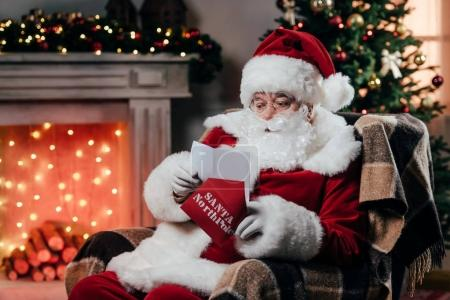 Photo for Santa claus in traditional red costume reading letter while sitting in armchair - Royalty Free Image