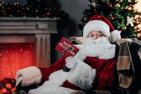 Photo for Santa claus in traditional red costume holding red envelope while sitting in armchair - Royalty Free Image